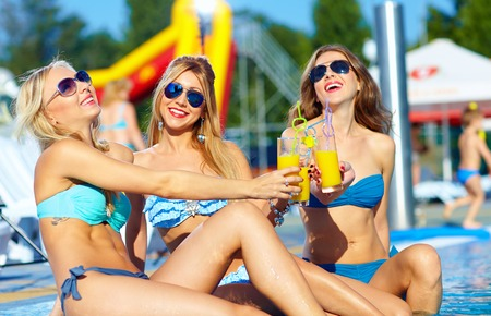 happy female friends enjoying summer near the pool photo