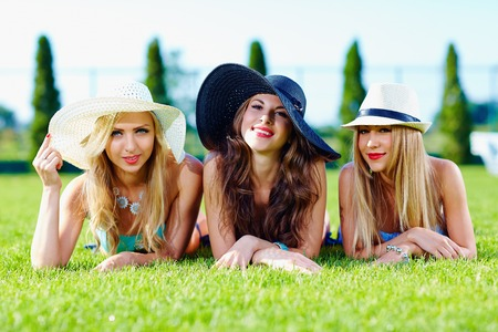 beautiful girls in hats relaxing on summer meadow photo