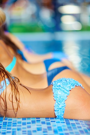 row of seductive female bodies in pool photo