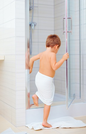 shower stall: cute kid ready to wash himself in shower Stock Photo