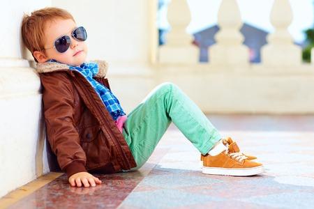 leuke modieuze jongen in leren jas en gum schoenen Stockfoto