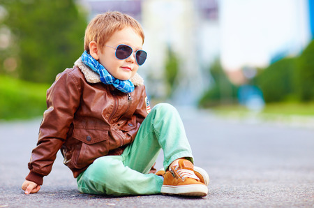 wear: cute stylish boy in leather jacket sitting on the road Stock Photo