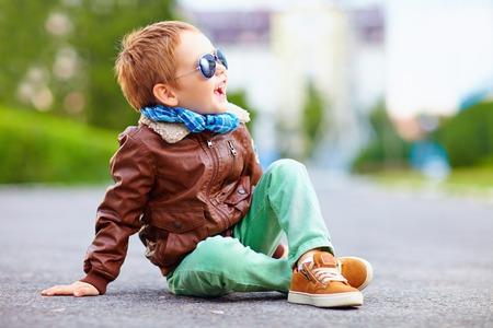 happy boy in leather jacket posing on the ground Standard-Bild