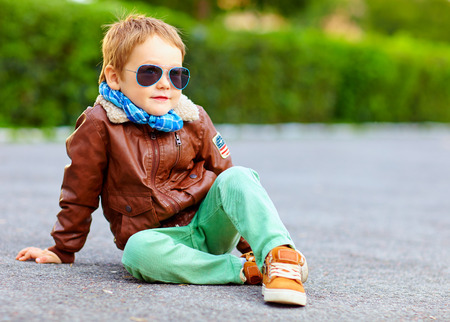 sitting on the ground: stylish boy in leather jacket posing on the ground Stock Photo