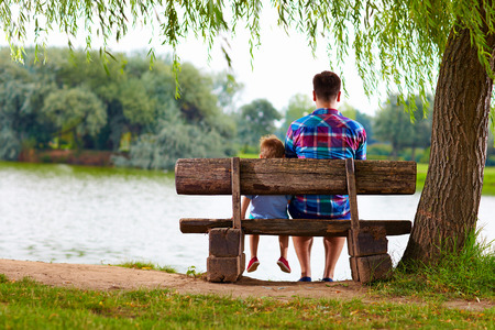 père et fils assis sur le banc au bord du lac