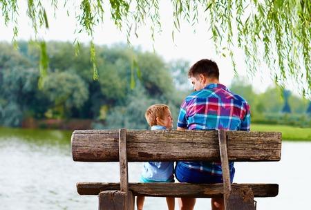 vader en zoon zitten op de bank in de buurt van het meer Stockfoto