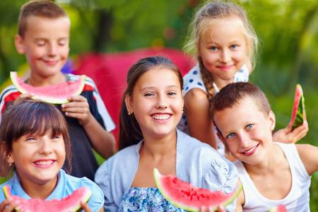 campamento: amigos felices comiendo sandía, al aire libre