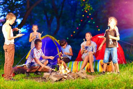 fogatas: felices los niños alrededor de la hoguera en un campamento de verano Foto de archivo