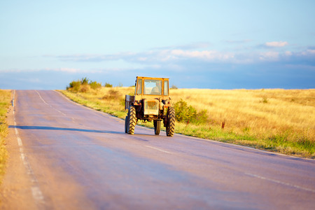 old tractor: farmer drives tractor on summer road