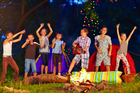 happy kids dancing around campfire