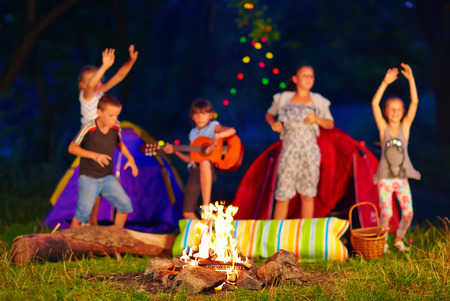 kids having fun around campfire. focus on fire photo