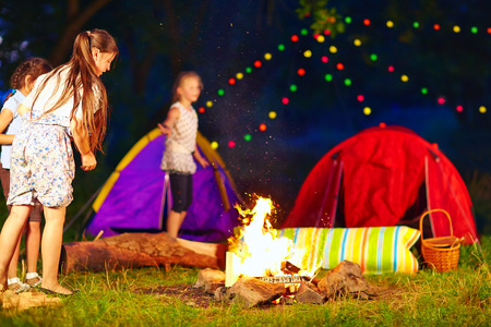 kids throwing wood in campfire, summer camp Stock Photo