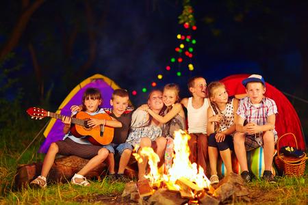 fogatas: felices los niños cantando canciones alrededor del fuego del campamento Foto de archivo