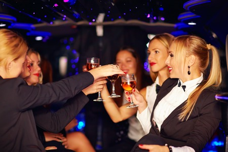 inside of: beautiful women clinking glasses in limousine Stock Photo