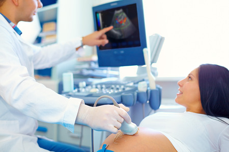 doctor conducting the ultrasound procedure to pregnant woman Banco de Imagens