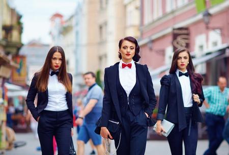labios rojos: hermosas chicas en trajes negros que caminan la calle Foto de archivo