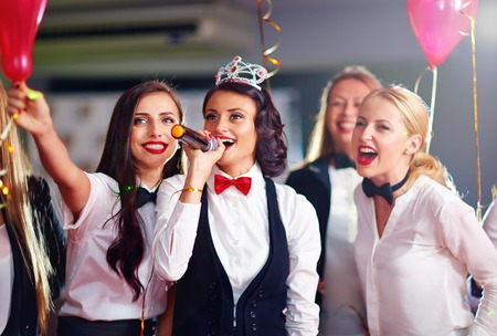 hen party: group of girls friends having fun on karaoke party Stock Photo