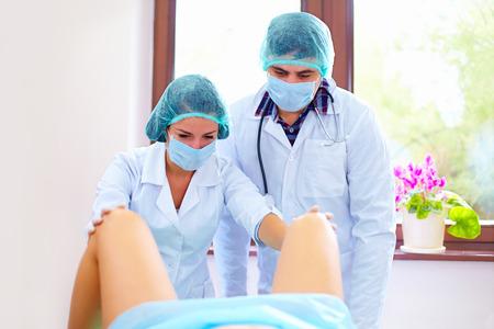病院で出産を取る医師