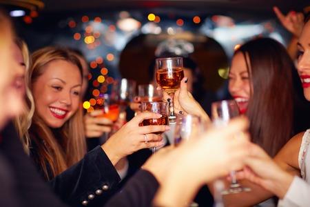 fiesta: mujeres hermosas que tintinean los vidrios en limusina. centran en las gafas Foto de archivo