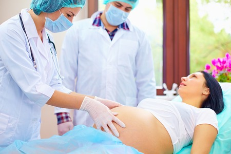 sala parto: medico palpa l'addome della donna incinta durante il parto
