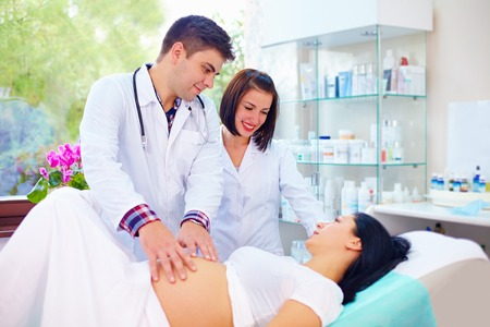 pielęgniarki: Lekarz palpates brzucha kobiety w ciąży przed porodem