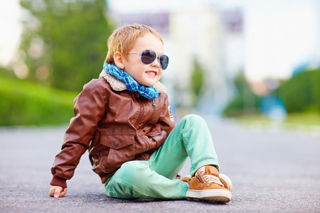 sitting on the ground: cute stylish boy in leather jacket sitting on the road Stock Photo