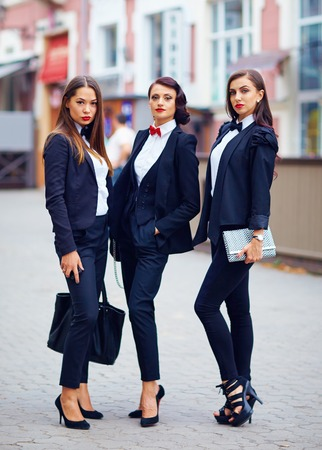 hair tie: beautiful girls in black suits posing on the street Stock Photo