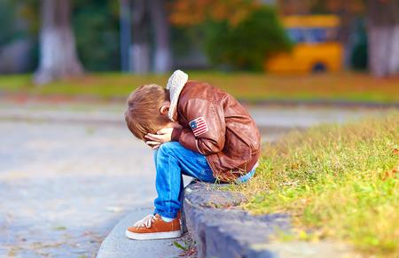pardon: bouleversé enfant garçon assis seul dans le parc de la ville Banque d'images