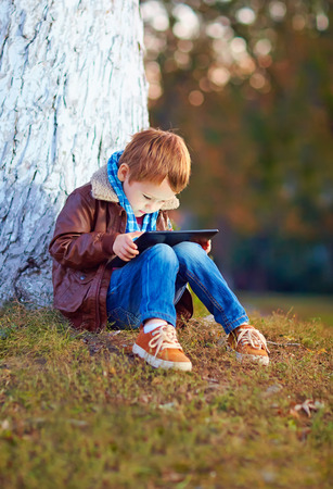 play ground: happy stylish boy playing on media tablet in city park Stock Photo