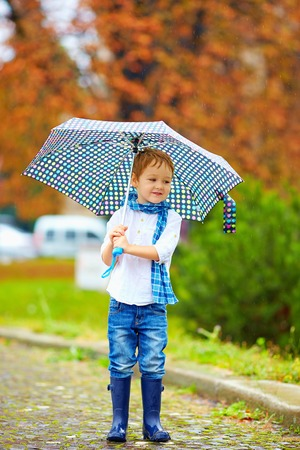 kids wear: cute kid with umbrella in park, rainy weather