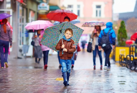 cute boy with umbrella walking on crowded city street