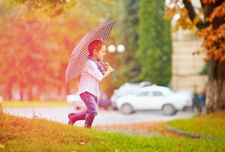 brolly: cute boy enjoying an autumn rain in city park