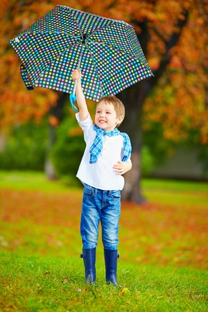 brolly: happy boy walking under an autumn rain