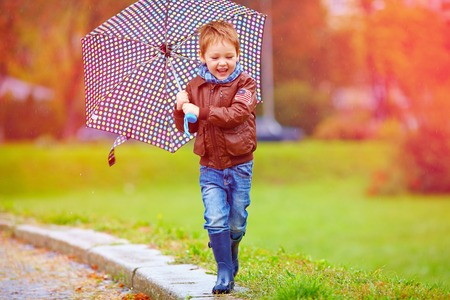 young boy smiling: happy boy running under an autumn rain
