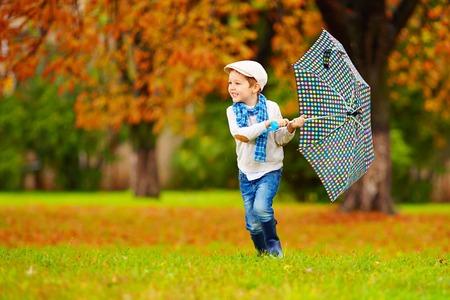 brolly: happy boy enjoying an autumn rain in park Stock Photo