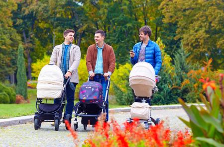 Tres amigos, padres caminando con buggies en parque de la ciudad Foto de archivo - 32315974