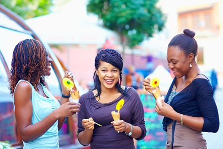 ice cream woman: happy african friends eating ice cream outdoors