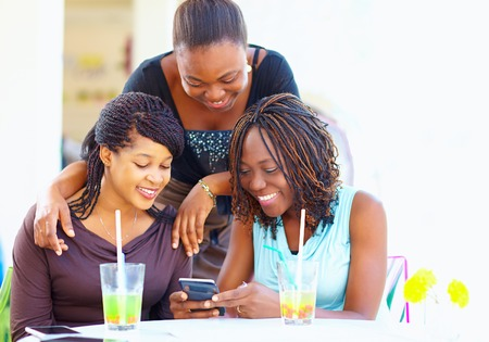 Talking on the phone: happy african friends chatting in social network