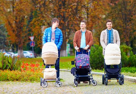 ojcowie spacery z buggy w parku miejskim, urlopy rodzicielskie