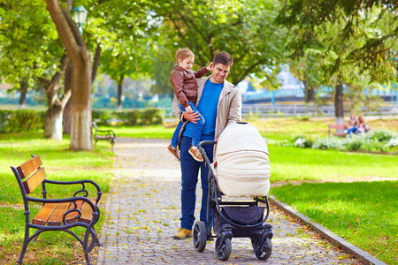 father with kids walking in city park