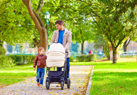 parental: father with kids walking in city park