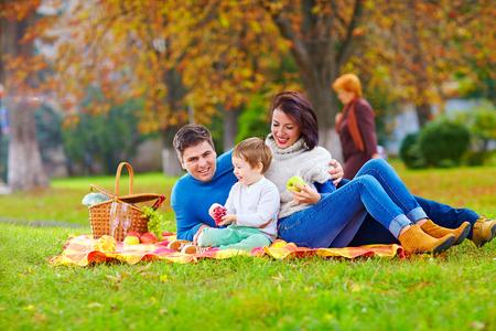 family picnic: familia feliz junto en picnic de otoño