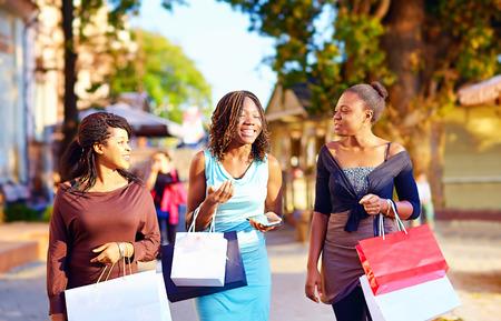 ショッピング バッグで街を歩く幸せなアフリカの女の子