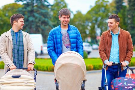 Los padres jóvenes con cochecitos de bebé en la ciudad a pie Foto de archivo - 32548500