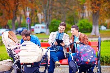 都市にベビーカーを持つ若い父親を歩く