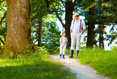 father and son walking rural path in forest photo