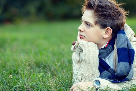 knappe tiener jongen ligt op gras en denkt Stockfoto