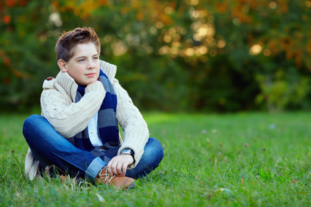 portrait of handsome teenager boy on green grass Stock Photo