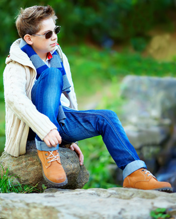 fashionable sunglasses: stylish teenage boy sitting on rock outdoors