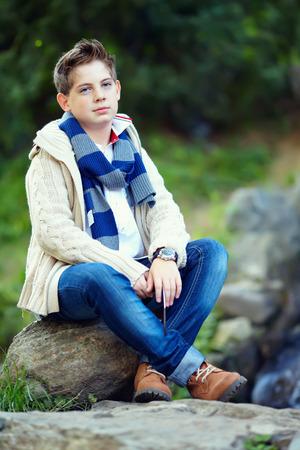 'teenager boy: stylish teenage boy sit on rock, nature outdoors Stock Photo